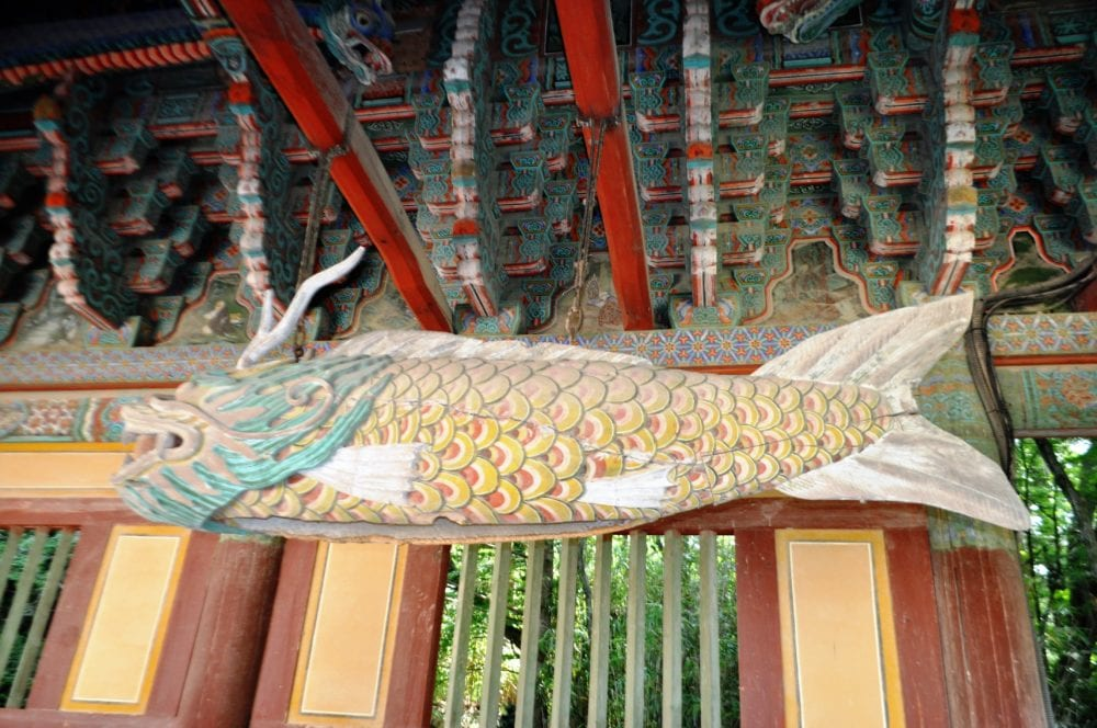 A carved fish hanging from the brightly decorated underside of a temple roof in Gyeongju, South Korea