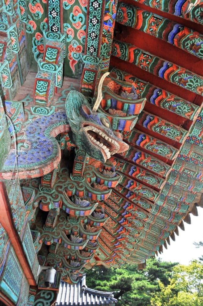 The brightly decorated underside of a temple roof with dragons in Gyeongju, South Korea