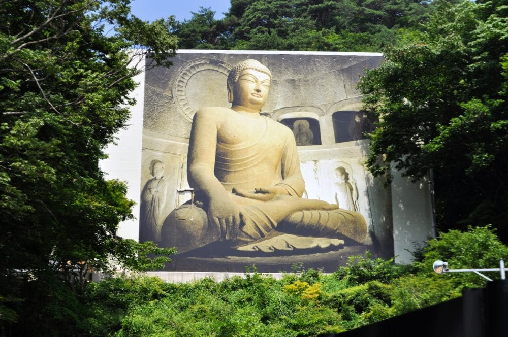 A giant buddha picture covers renovation work at temple buildings in Gyeongju South Korea