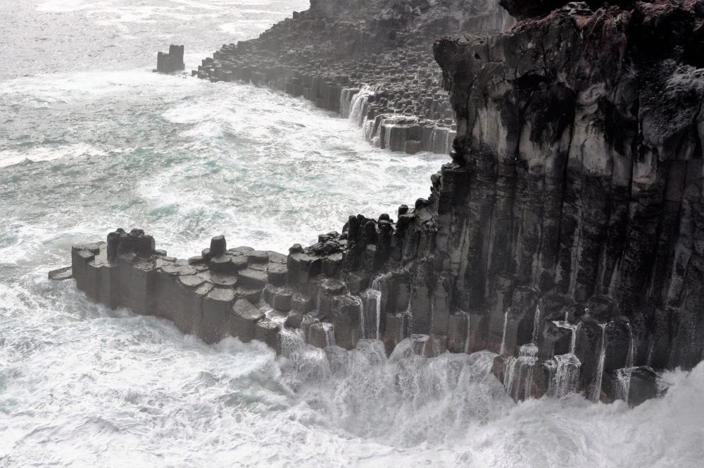 Foaming sea around basalt pillars on Jeju, South Korea