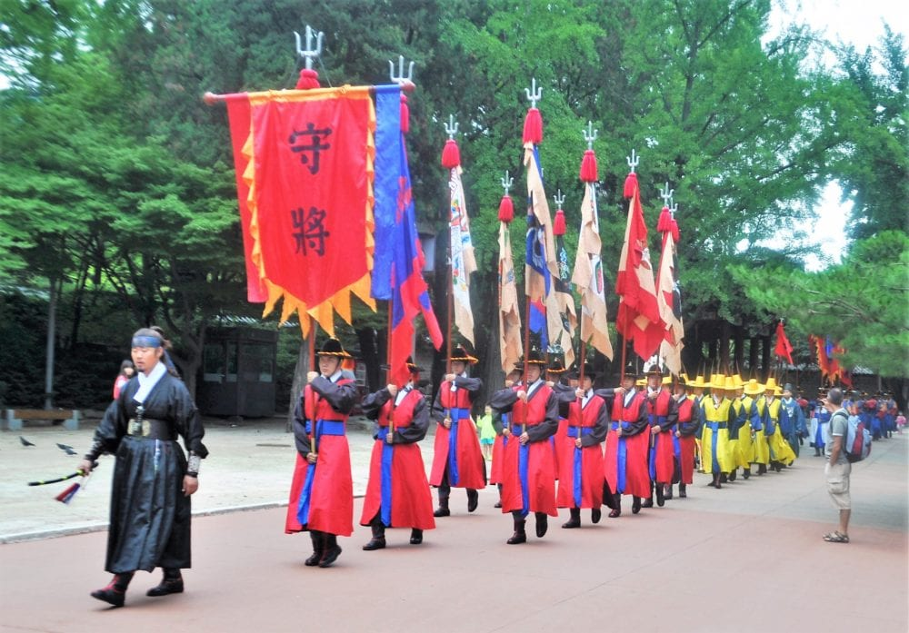 Banners carried by hanbok wearing men at the changing of the guard, Deoksugung Palace, Seoul