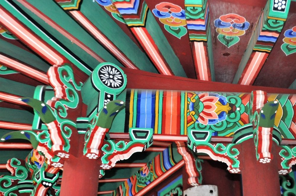 The brightly decorated underside of a roof in a temple in Seoul, taken close up