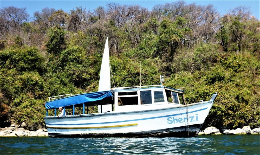 Shenzi, the wooden snorkelling boat moored by a tree covered island on Lake Malawi