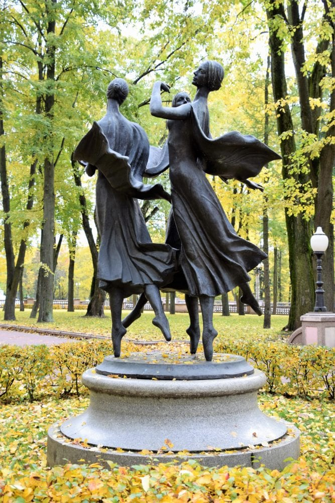 Metal sculpture of two ballerinas in a park