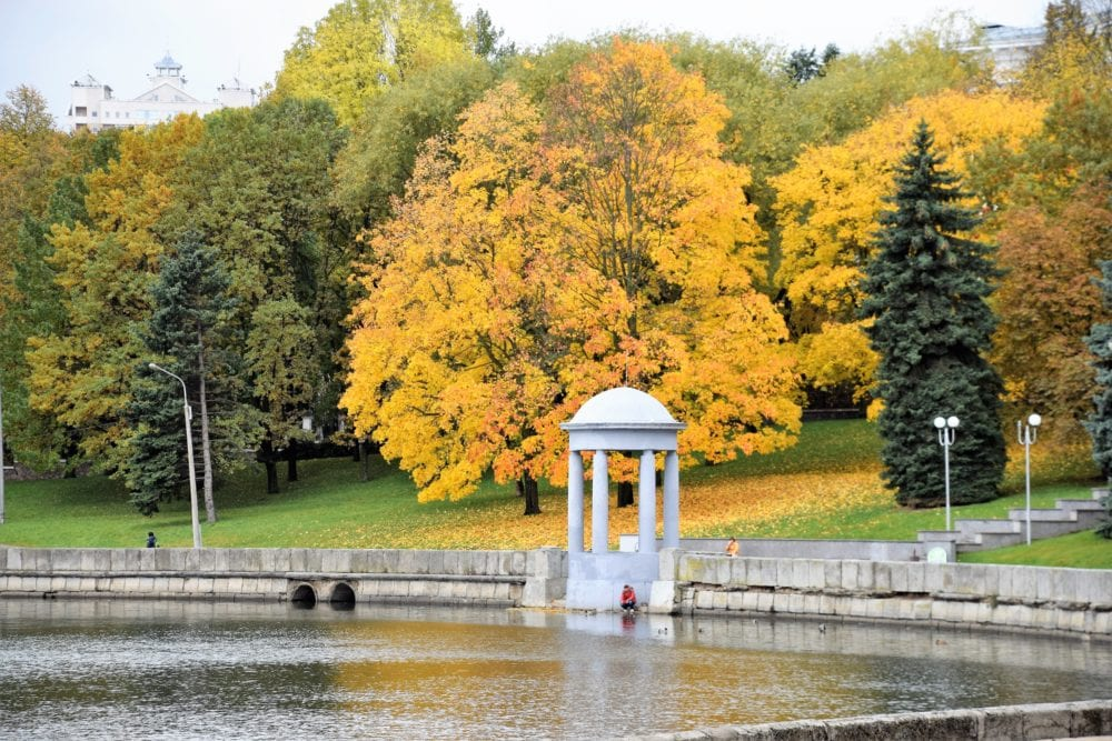 A neo classical folly on the edge of a lake in Minsk beautifully set off by orange yellow trees in autumn