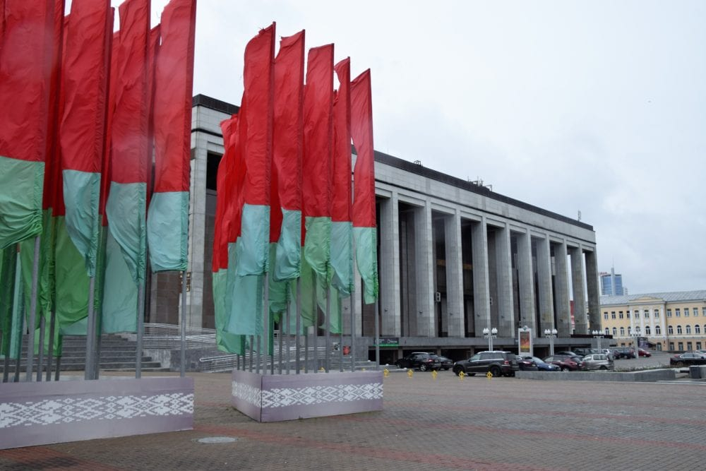 The pillared facade of the Minsk Palace of the Republic, stands of red and green flags to the left