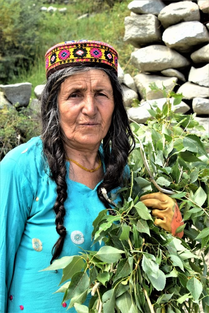 A headshot of a lady with long plaits and a skull cap in the Hunza Valley