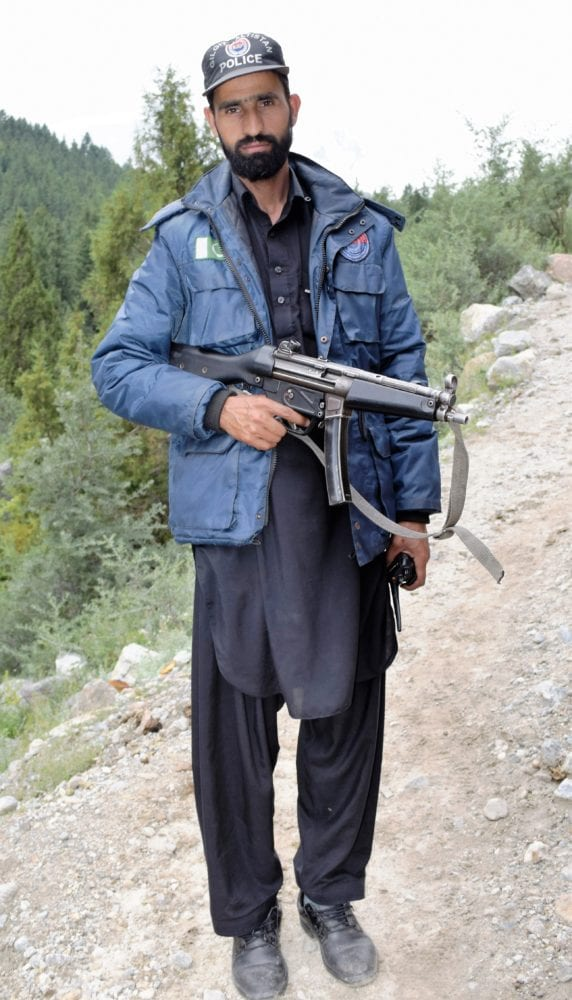 A guard carrying his AK47 up the mountain