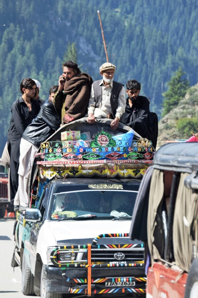 Travellers crammed into the back of a decorated pick up truck in Pakistan