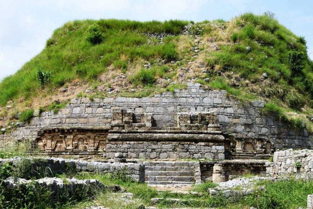 Grass covers the remains of a stone stupa at Taxila, Pakistan