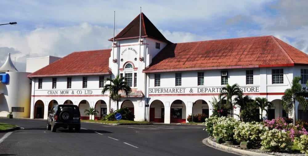 The white arched facade and tower of a row of shops in Apia, Samoa
