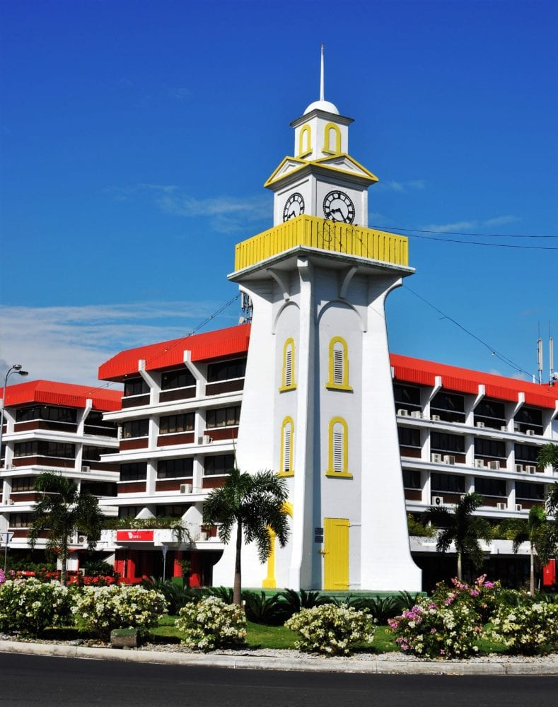 A yellow and white clocktower in Apia, Samoa, against a bright blue sky