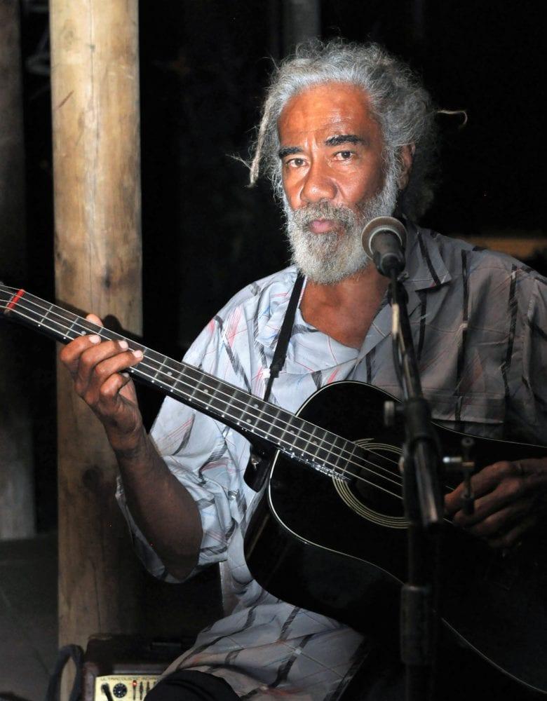 A three quarter shot of a man with grey ahir and beard playing guitar