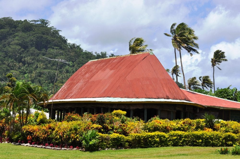 Neat hedging round a red roofed meeting hosue in a Samoan village