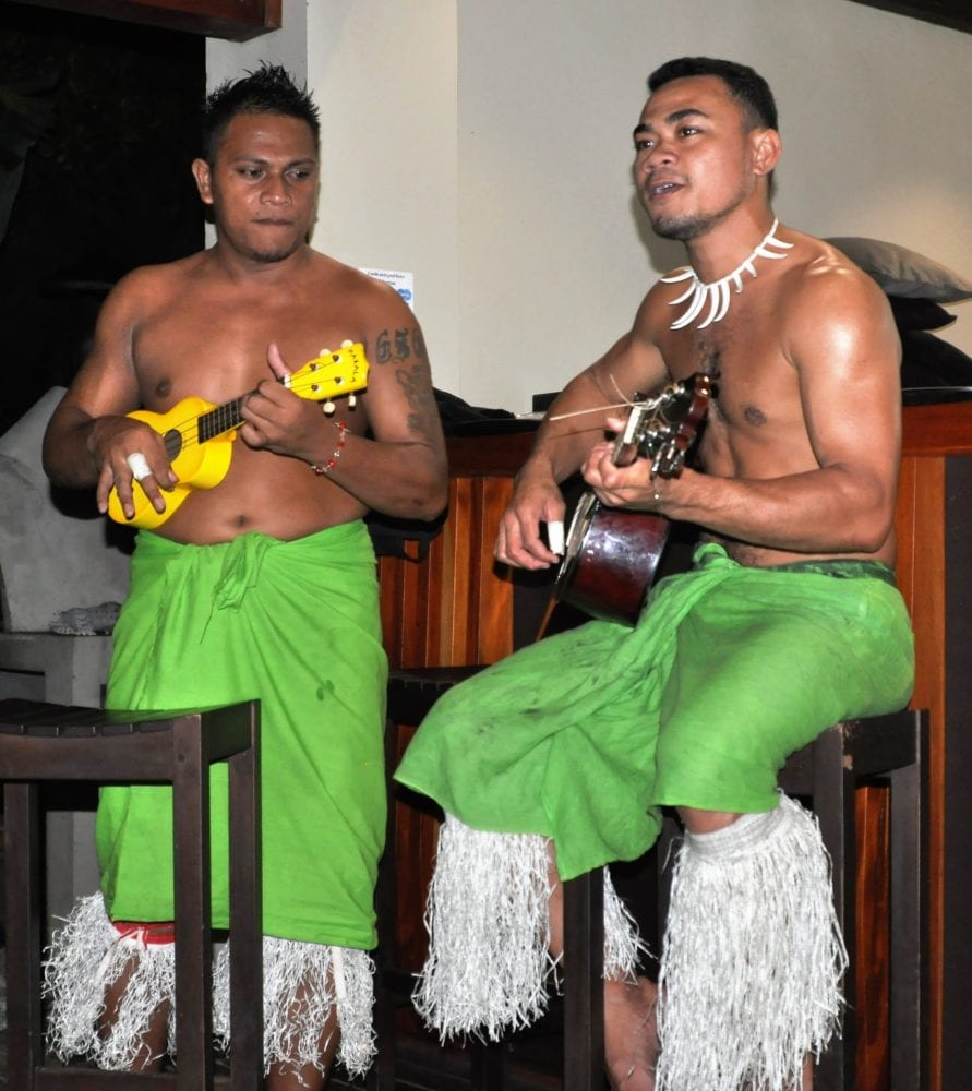 Two bare chested Samoan musicians in green sarongs