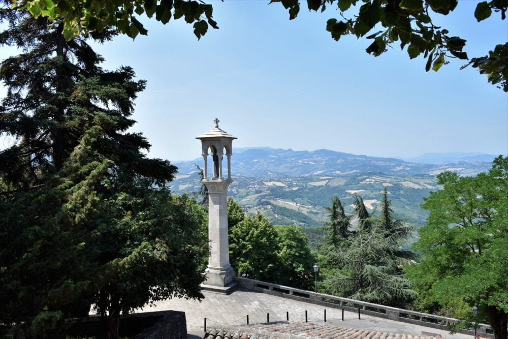 A shrine in front of the view across the hills of San Marino
