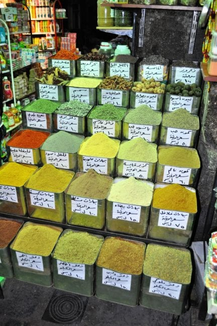Colourful green and yellow spices displayed in tins in the souk at Damascus