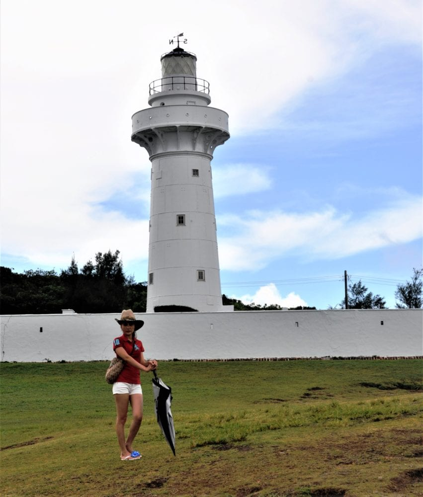 A lady in shorts and cowboy hat poses in front of Eluanbi Lighthouse