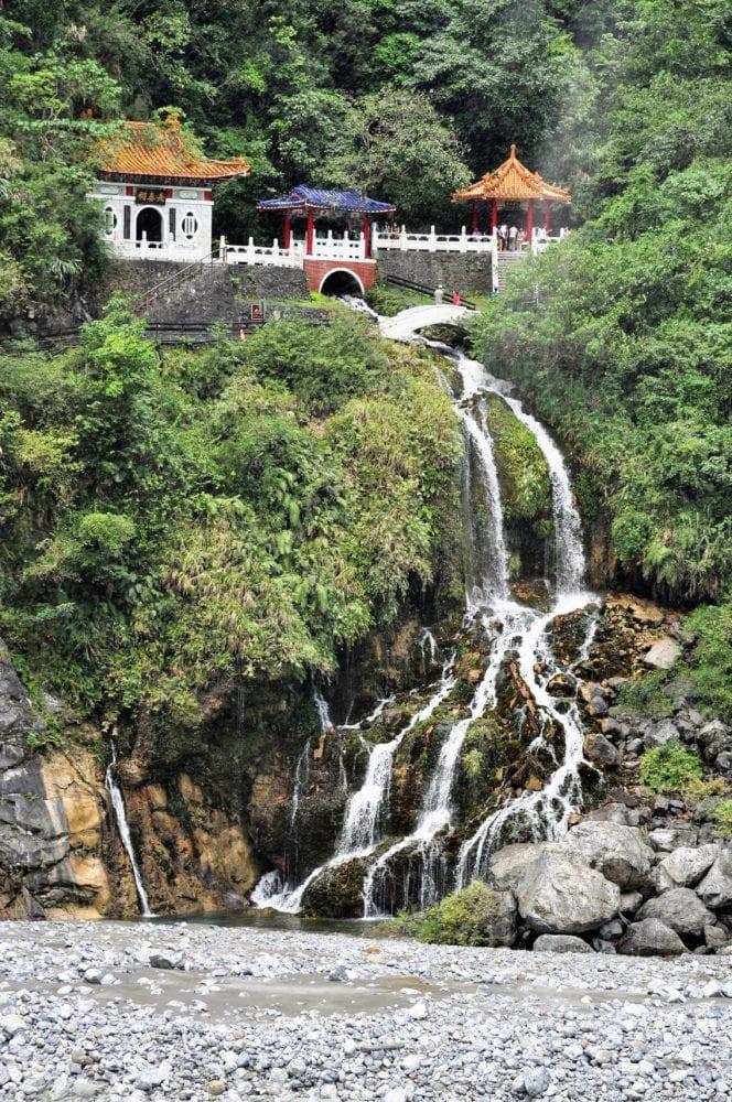 A waterfall falls into Taroko Gorge below a Tao Temple