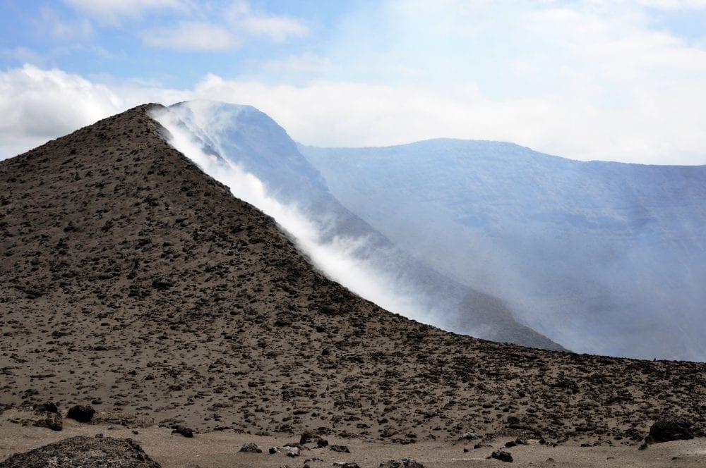 Tendrils of smoke creeping over part of the crater edge at Mount Yasur, Vanuatu