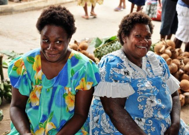 Shy smiling ladies in floral dresses at Port Vila market, Vanuatu