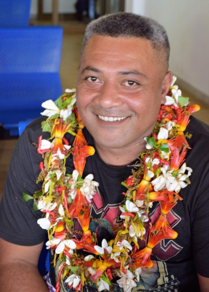A Wallisian man wearing a flower garland