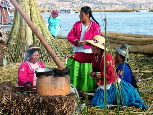 Local women cooking round an open pot at Lake Titicaca