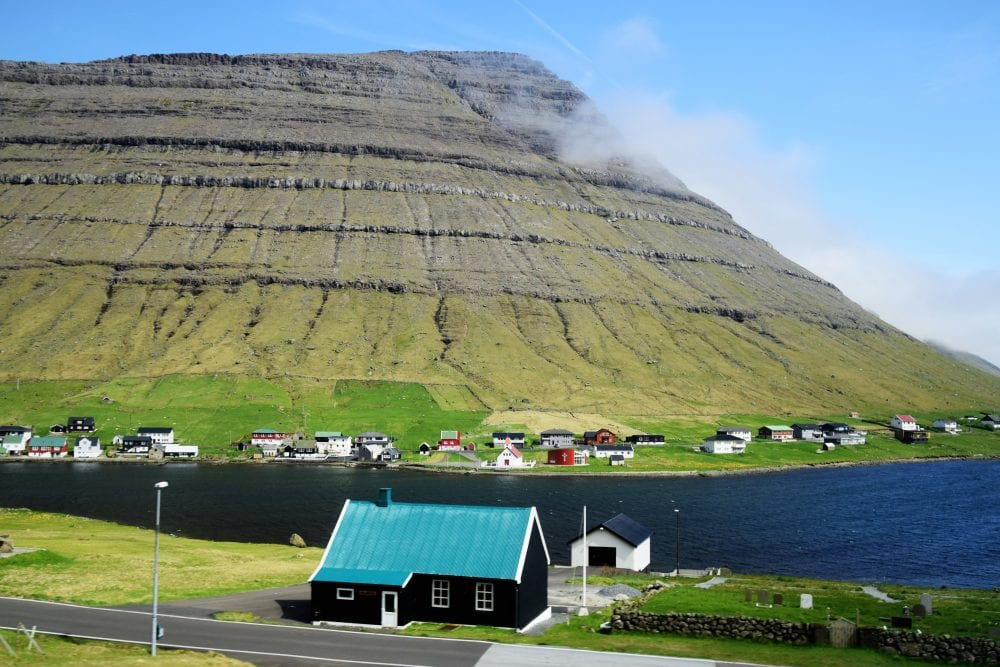 Clouds passing in front of a steep velvety sided fjord, Faroe Islands