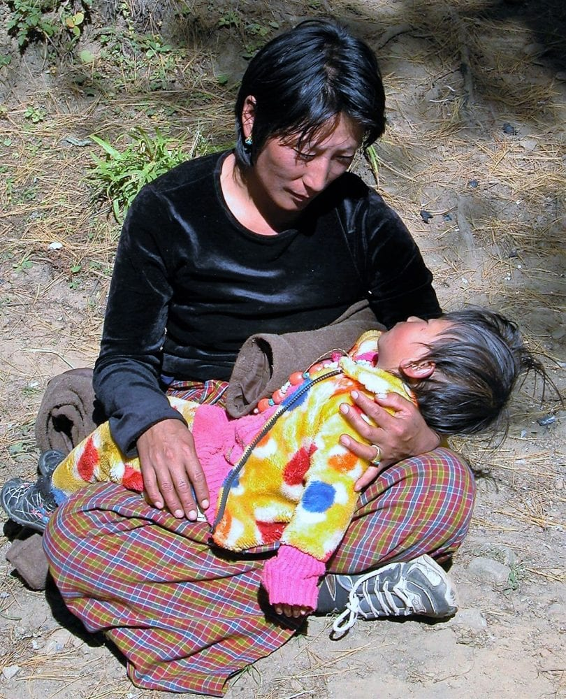 A Bhutanese mother holds her sleeping baby on her lap