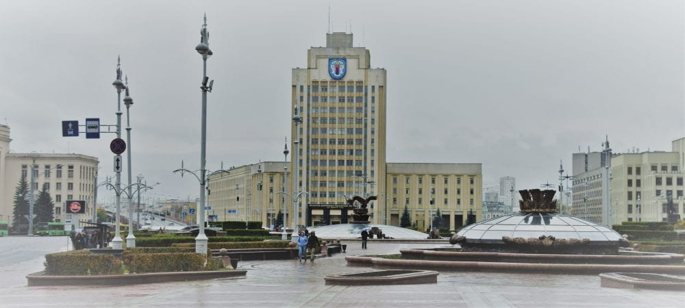 A view across the domed metal mounments of Independence Square in Minsk to yellow Soviet buildings