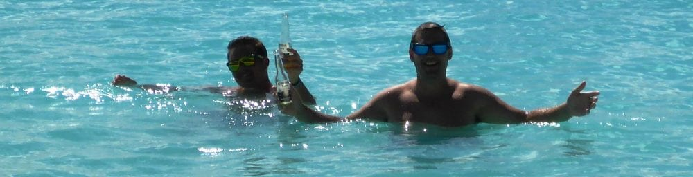 Jesse and Elias in the sea with their bottles at White Bay Beach Jost Van Dyke
