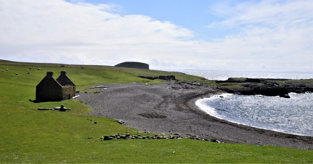 The grey shingle beach and derelict cottage at Stenness, Shetland