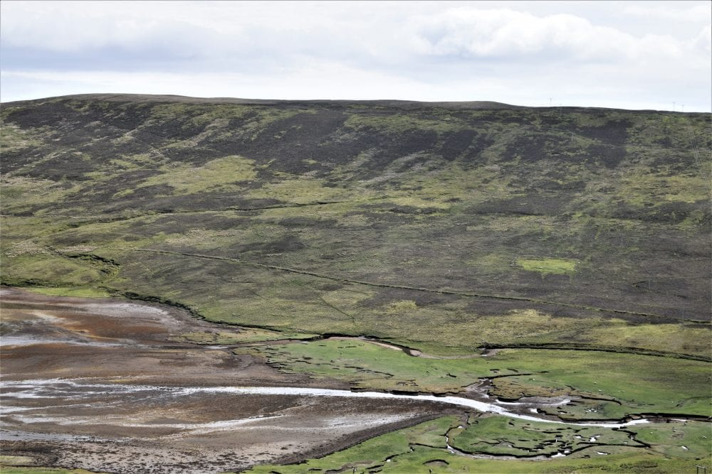 Steep rugged hillsides form a narrow valley in mid mainland Shetland