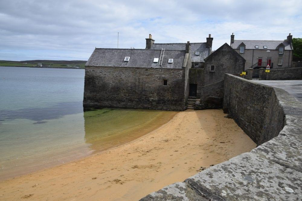 The beautiful tiny sandy beach next to 'Jimmy Perez House' in Shetland