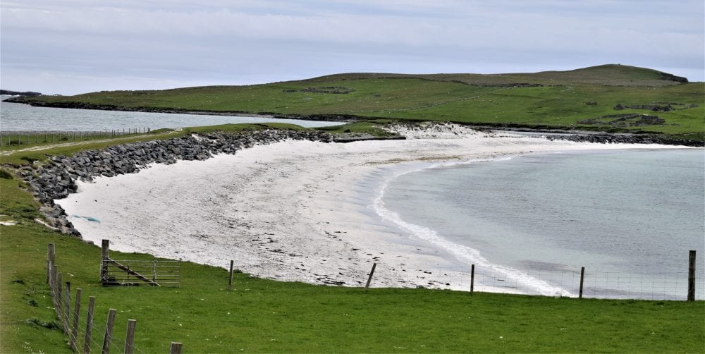An arc of white sand , the Minn Beach tombolo with the hills of Kettla Ness behind