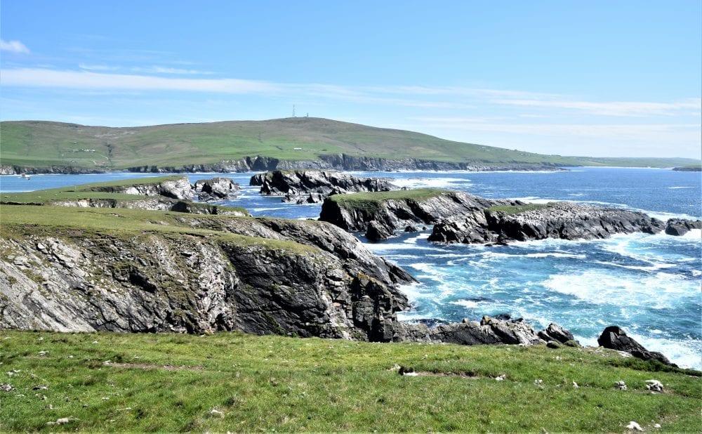 Craggy rocks and foaming mixed blue seas at St Ninian's Isle, Shetland