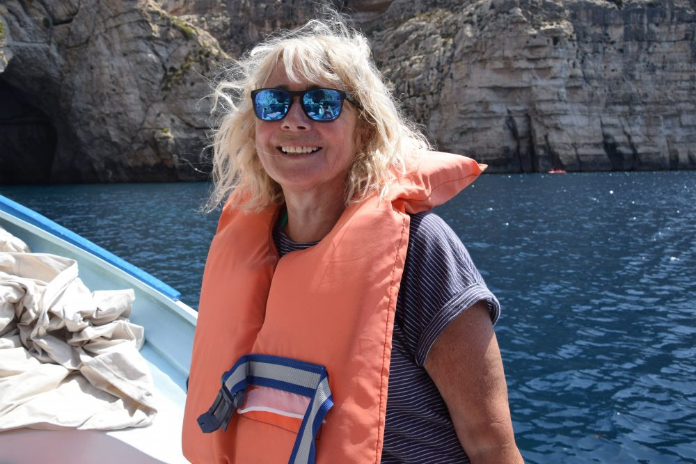 Sue with windswept hair on the boat at the Blue Grotto, Malta