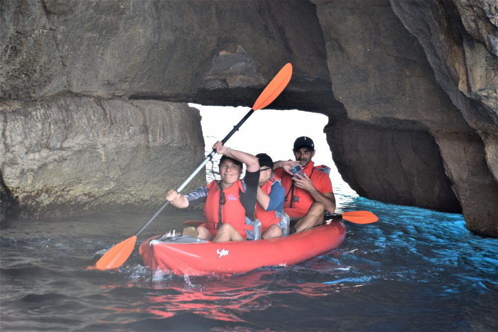 Tourists float a kayak through an arch at the Blue Grotto, Malta