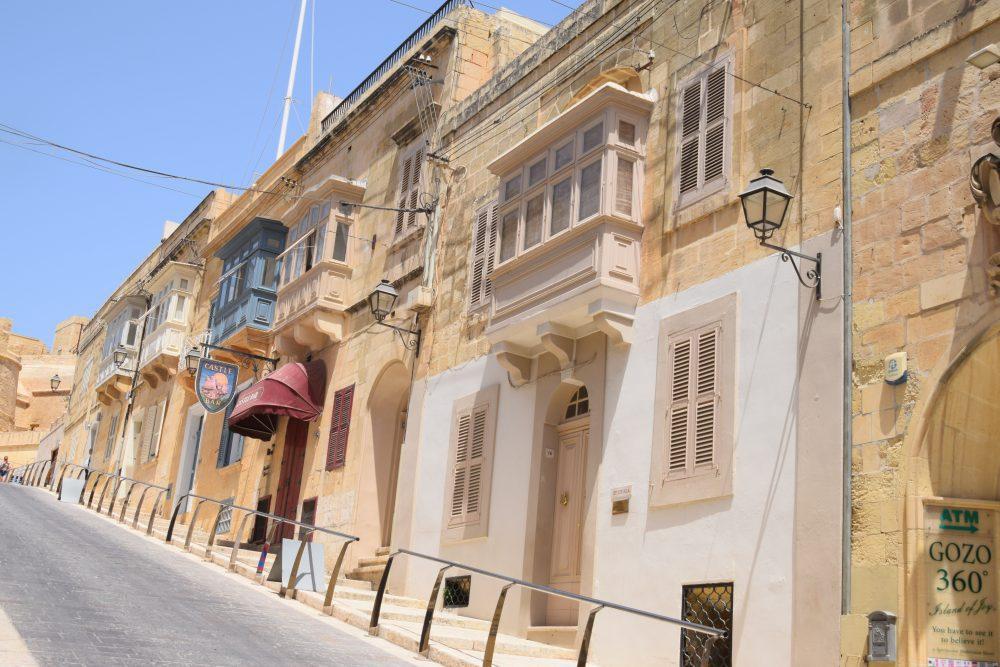 Covered balconies on a steep street in Rabat, Gozo