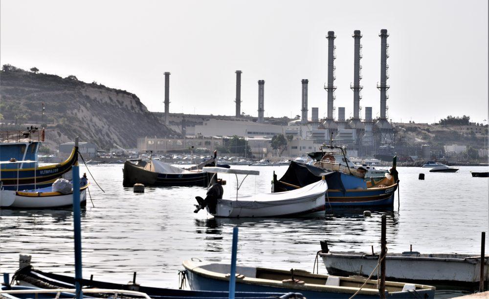A power station forms the backdrop to the bay at Marsaslokk, Malta
