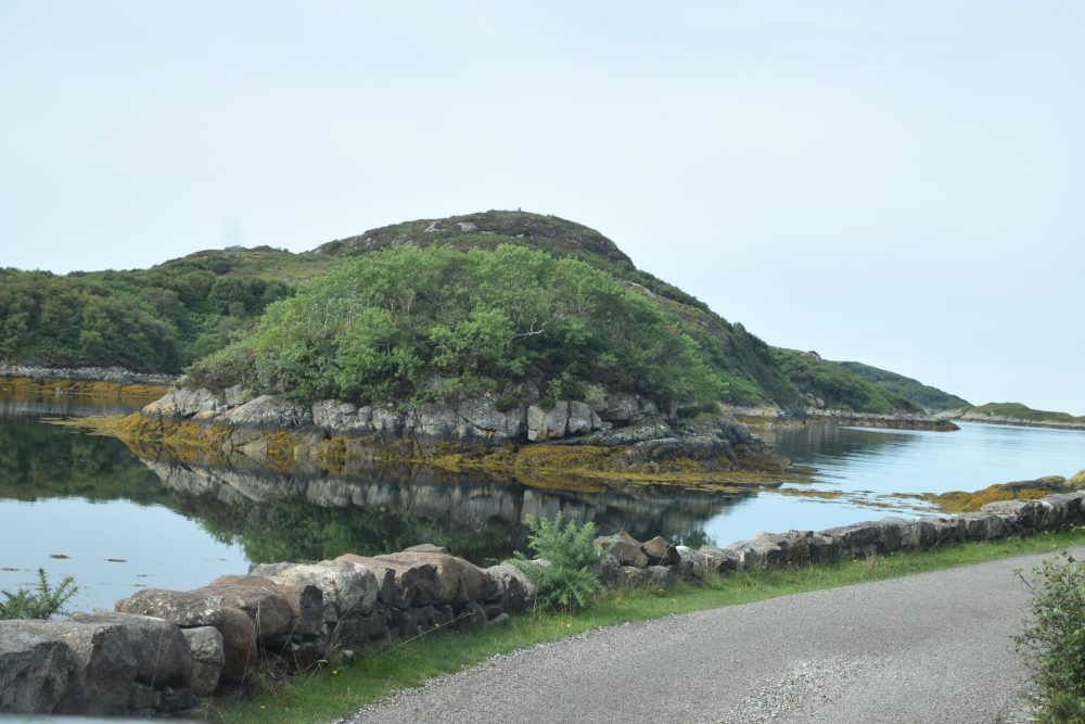 An islet reflected in a loch, north west Scotland