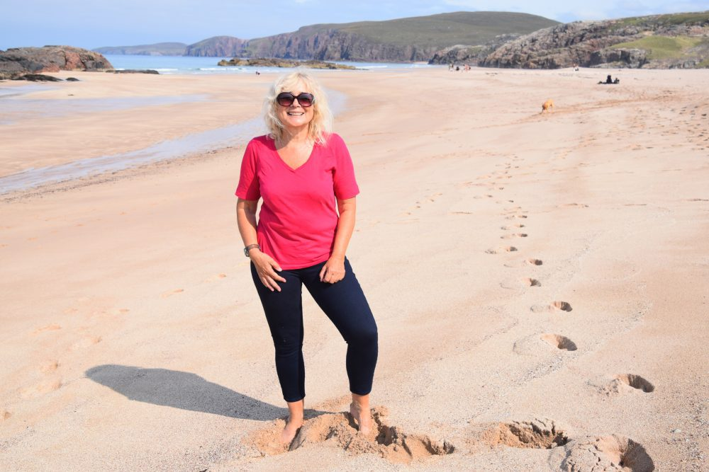 Sue in front of the cliffs and the sweep of sand at Sandwood Bay Beach, Scotland