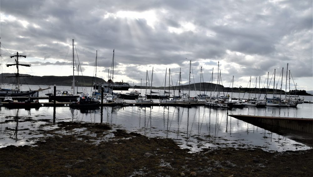 The ferry leaves Oban at twilight, masts of boats reflected in the water