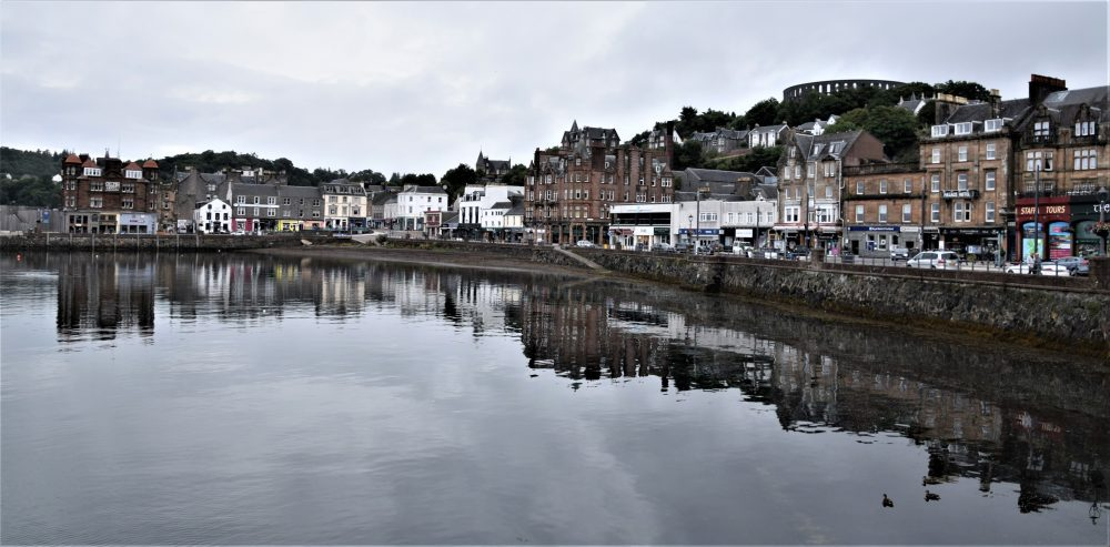 A panoramic view of Oban high street across the water, buildings reflected in the sea
