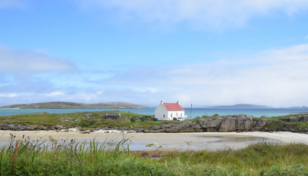 Beautiful turquoise seas frame a red roofed cottage on Barra