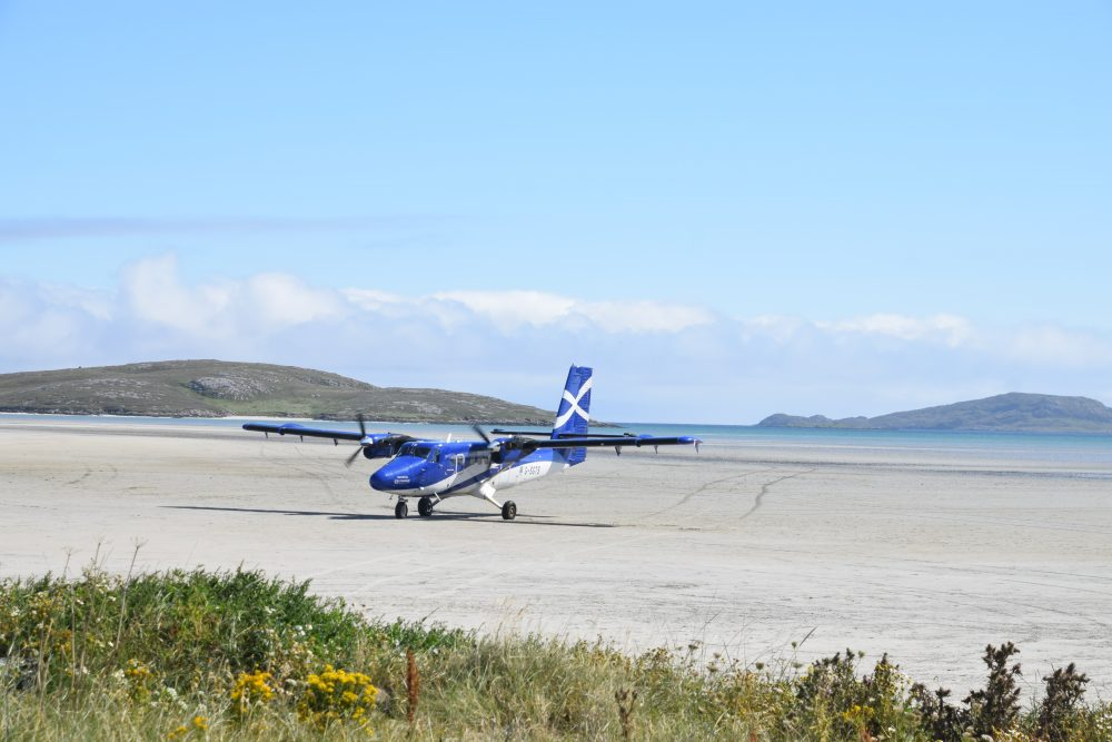 The twin otter plane lands on the sand at Barra Airport