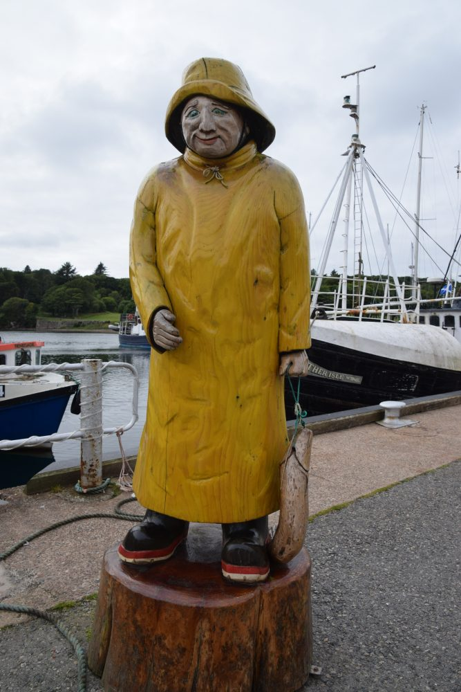 A statue wears oilskins in Stornoway Harbour, Lewis, Western Isles